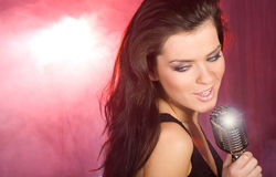 Het zingen van het meisje in retro mic stock afbeeldingen