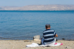 Het zitten op het strand Stock Foto