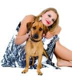 Het zittingsmeisje met een geïsoleerder hond Stock Foto