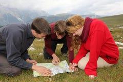 Het zoeken van de bestemming op een kaart in de bergen stock foto's