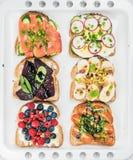 Het zoete en smakelijke assortiment van ontbijttoosts De sandwiches met fruit, groenten, eieren, rookten zalm bij het witte bakse royalty-vrije stock fotografie