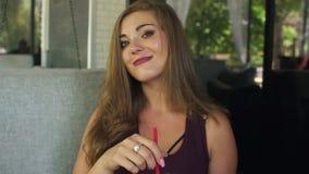 Het zoete jonge meisje met bovenmatige gewichtsdranken koelt limonade in een koffie van de de zomerstraat stock video