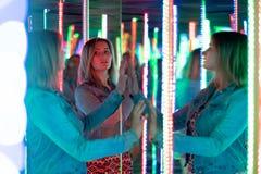 Het zoete Kaukasische meisje loopt in een spiegellabyrint met kleurrijke dioden en geniet van een ongebruikelijke aantrekkelijkhe stock foto's