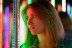 Het zoete Kaukasische meisje loopt in een spiegellabyrint met kleurrijke dioden en geniet van een ongebruikelijke aantrekkelijkhe royalty-vrije stock fotografie