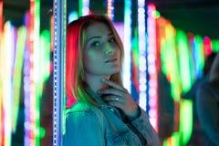 Het zoete Kaukasische meisje loopt in een spiegellabyrint met kleurrijke dioden en geniet van een ongebruikelijke aantrekkelijkhe stock afbeelding