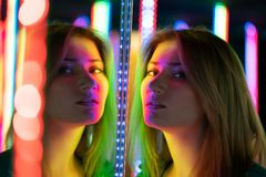 Het zoete Kaukasische meisje loopt in een spiegellabyrint met kleurrijke dioden en geniet van een ongebruikelijke aantrekkelijkhe stock foto