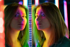 Het zoete Kaukasische meisje loopt in een spiegellabyrint met kleurrijke dioden en geniet van een ongebruikelijke aantrekkelijkhe stock fotografie
