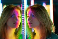 Het zoete Kaukasische meisje loopt in een spiegellabyrint met kleurrijke dioden en geniet van een ongebruikelijke aantrekkelijkhe royalty-vrije stock foto's
