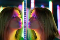 Het zoete Kaukasische meisje loopt in een spiegellabyrint met kleurrijke dioden en geniet van een ongebruikelijke aantrekkelijkhe stock afbeeldingen