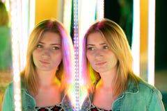 Het zoete Kaukasische meisje loopt in een spiegellabyrint met kleurrijke dioden en geniet van een ongebruikelijke aantrekkelijkhe royalty-vrije stock afbeelding