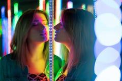 Het zoete Kaukasische meisje loopt in een spiegellabyrint met kleurrijke dioden en geniet van een ongebruikelijke aantrekkelijkhe royalty-vrije stock afbeeldingen