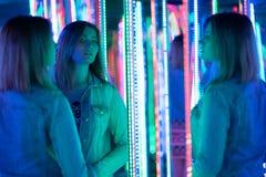 Het zoete Kaukasische meisje loopt in een spiegellabyrint met kleurrijke dioden en geniet van een ongebruikelijke aantrekkelijkhe royalty-vrije stock foto