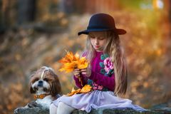 Het zoete meisje in een hoed weeft een kroon van de bladeren van de de herfstesdoorn stock foto
