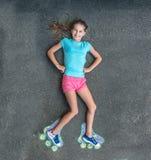 Het zoete meisje in rolschaatsen schilderde met krijt stock foto's