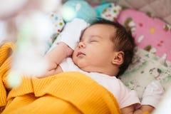 Het zoete pasgeboren babymeisje slaapt in haar voederbak stock fotografie