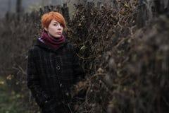 Het zoete roodharige meisje in een zwarte laag en een purpere gebreide sjaal bevindt zich door de omheining die met wijnstok of k royalty-vrije stock fotografie