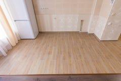 Het in zones onderver*delen van vloer in binnenlandse, ceramische keukentegels grenste met gelamineerde bevloering in de woonkame stock foto's