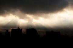 Het zonlicht glanst door donkere wolk met silhouet van de bouw Royalty-vrije Stock Fotografie