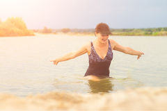 In het zonlicht het meisje in het zwempak uit het water Royalty-vrije Stock Foto