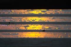 Het zonlicht is het kostbaarste goud dat op Aarde, gouden licht op een houten die bank moet worden gevonden met regendruppeltjes  royalty-vrije stock afbeelding