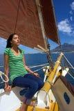 Het zonnebaden van meisje op jacht met rode zeilen Stock Foto
