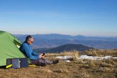 Het zonnepaneel aan de tent wordt verbonden die De mensenzitting naast mobiele telefoonlasten van de zon Stock Fotografie