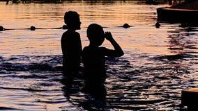Het zonsondergangsilhouet van gelukkige kinderen geniet water van spelen in poo Stock Foto's