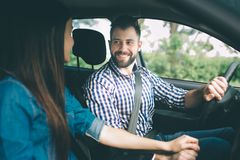 Het zorgvuldige drijven Mooie jonge paarzitting op de voorpassagierszetels en het glimlachen terwijl knappe mens die a drijven stock afbeelding