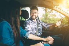 Het zorgvuldige drijven Mooie jonge paarzitting op de voorpassagierszetels en het glimlachen terwijl knappe mens die a drijven stock foto