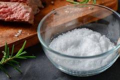 Het zout in glaskom voor maakt rundvleeslapje vlees Stock Afbeeldingen
