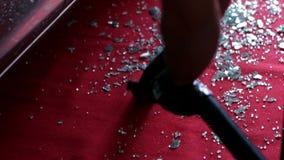 Het zuigen van de smal stukken van een gebroken venster die op het rode tapijt leggen stock videobeelden