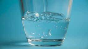 Het zuivere water wordt gegoten in een glas transparant glas stock videobeelden