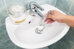 Het zuiveringszout wordt gegoten aan deblokkeert thuis drainagesysteem dat Stock Foto