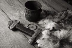 Het zwaard en de stenen bierkroes van Viking op een bont stock afbeeldingen