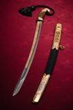 Het zwaard van Ornated op rood stock foto's