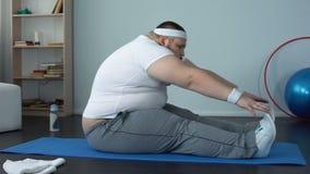 Het zwaarlijvige mannelijke uitrekken zich op mat na huistraining, spiertoon, lichaamsflexibiliteit stock video