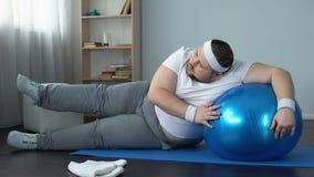 Het zwaarlijvige mannelijke worstelen om het programma van de huistraining, geschiktheidsroutine, doel te beëindigen stock footage
