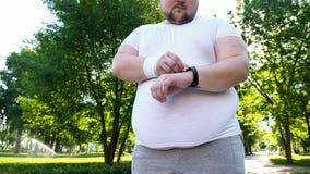 Het zwaarlijvige mens tarief van het controlehart op smartwatch na jogging, app voor gezondheidszorg royalty-vrije stock foto