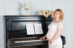 Het zwangere blondemeisje speelt de piano Stock Fotografie