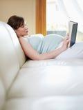 Het zwangere boek van de vrouwenlezing thuis stock fotografie