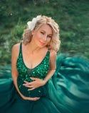Het zwangere jonge meisje met blond haar verfraaide met verse bloemen, glimlachen leuk in de camera, het houden van en het koeste royalty-vrije stock afbeelding