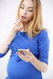 het zwangere meisje schildert lippen Stock Afbeeldingen