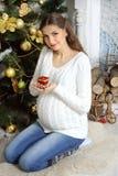 Het zwangere meisje zit op zijn overlapping en holding een kaars Stock Fotografie