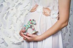 Het zwangere paard-speelgoed van de vrouwenholding dichtbij haar buik Stock Foto's