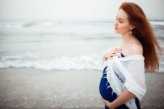 Het zwangere roodharigemeisje in een blauwe kleding en een witte sjaal is op de achtergrond van de oceaan Het mediteren op het ge Royalty-vrije Stock Fotografie