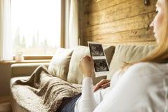 Het zwangere vrouw pasgeboren denken en het houden van ultrasone klank terwijl ly stock afbeeldingen