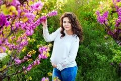 Het zwangere vrouw stellen in een bloeiende tuin royalty-vrije stock fotografie