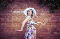 Het zwangere vrouw stellen tegen een muur van rode baksteen Royalty-vrije Stock Foto