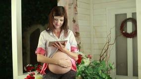 Het zwangere vrouw typen op aanrakingsstootkussen stock footage