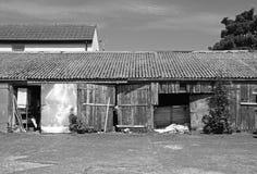 Het zwart-wit beeld van herstelde en herstelde sjofele landelijke workshop uit gebouwen met sjofele houten deuren met schil schil Royalty-vrije Stock Afbeelding